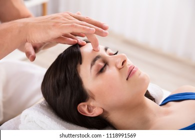 Close-up Of A Calm Young Woman Receiving Reiki Treatment In Spa
