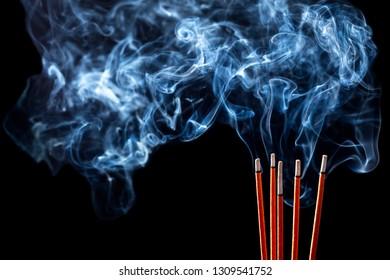 Closeup of calmly burning incense sticks with blue fume on black background