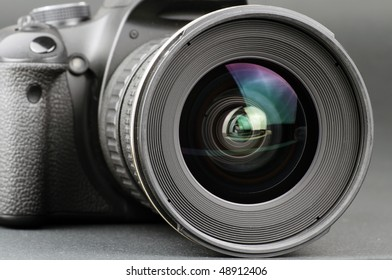 Close-up of a camera lens attached to a camera body on a black background