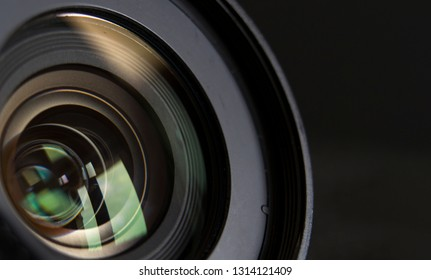 close-up camera lens and black background reflection