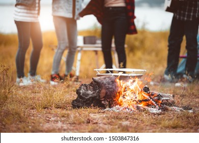 Closeup of campfire with friendship dancing to beat of the music for celebrating in party with mountain meadow and lake view background. People lifestyle and travel vacation. Picnic and camping tent
