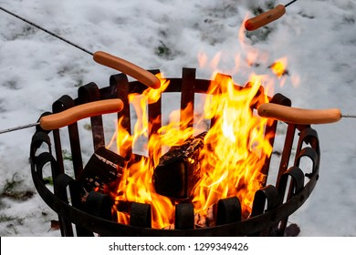 Closeup of a campfire with hot dog food over open fire. Winter snow outdoor scene.