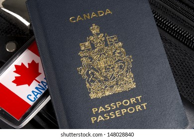 Closeup of Canadian passport sitting on suitcase with maple leaf luggage tag