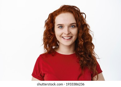 Close-up of candid smiling woman with red curly hair and pale healthy skin, looking cheerful at camera, standing in t-shirt against white background