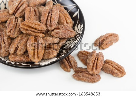 Closeup of candied pecans on a small dish on white background. Macro shot of pecans.