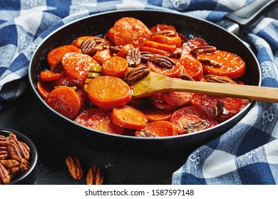 close-up of Candied sweet potatoes with brown sugar, maple syrup, orange juice and pecan nuts in a skillet with wooden spatula, view from above