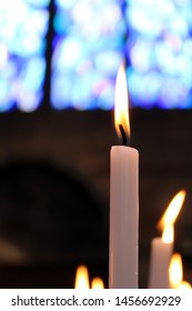 Close-up of a candle in a church, with more candles and a stained-glass window in the background, in soft focus in the background.