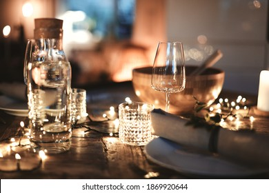 Closeup of a candlelit dining table set up with glasses and tableware for an evening dinner party