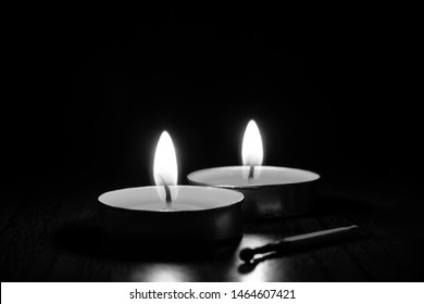Close-up candles burning in the black background. The concept of mourning, grief or sorrow. Black and white photo. Burnt match.