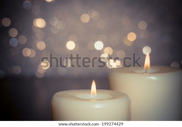 close-up of candles with flame on bokeh background and space for text