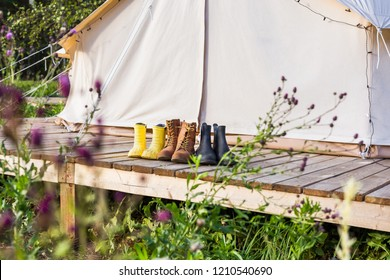 Close-up of a canvas bell tent with shoes on a wooden base outdoors