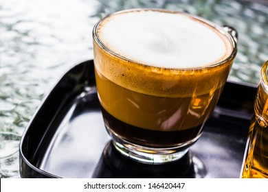 Closeup cappuccino coffee in glass cup on shiny iron table