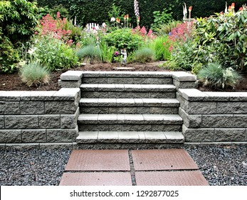 Closeup capture of a concrete block retaining wall with incorporated grey staircase integrated into an existing garden landscape design consisting of perennial flower planter and shrubs as  background