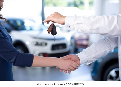 Close-up of car dealer shaking buyer's hand and giving keys after transaction