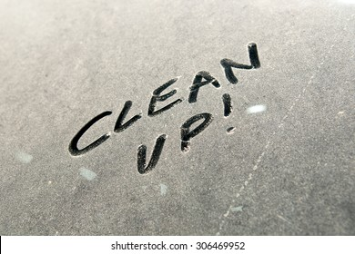 "Close-up of car dust with inscription ""CLEAN UP!"" word on a dirty glass window, top view."