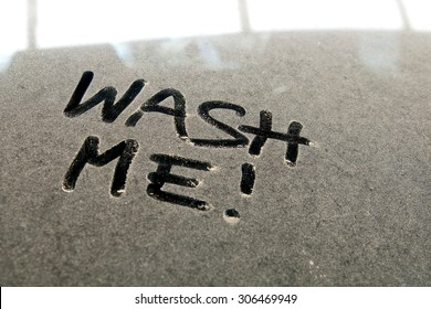 """Close-up of car dust with inscription """"WASH ME!"""" word on a dirty glass window, front view."""