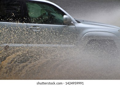 Closeup of a car explosively splashing through dangerously high water on a river flooded road