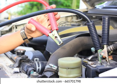 Close-Up Car mechanic uses battery jumper cables to car battery
