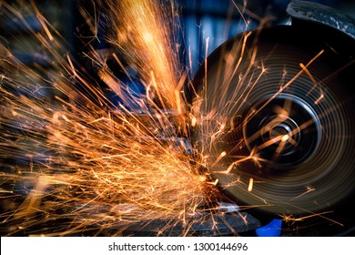A close-up of a car mechanic using a metal grinder to cut a car part  in an auto repair shop, bright orange flashes flying in different directions, in the background tools for an auto repair