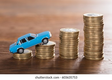 Close-up Of A Car Model On Stacked Coin At Wooden Desk