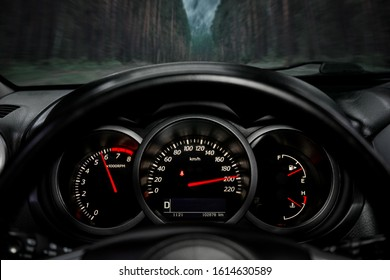 A close-up of a car panel with a speedometer indicating a huge speed of 200 km per hour, a tachometer at 6000 rpm, oil and gasoline levels. The car rides on the highway at high speed along the forest