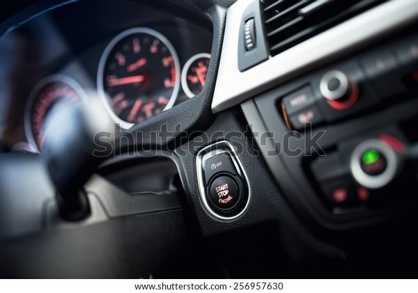 Nahaufnahme des Start- und Stoppknopfes. Modernes Autoinnere mit Dashboard und Cockpit-Details