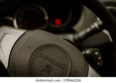 Close-up of car steering wheel with large airbag sign. car whistle on airbag safety sticker. Beware of passive safety devices in the vehicle.