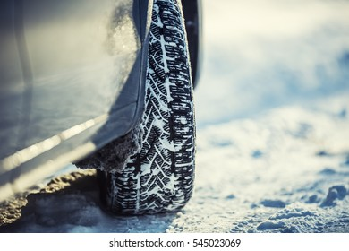 Closeup of car tires on a snowy road.