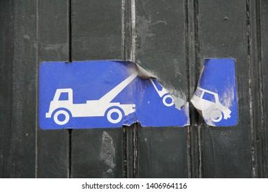 closeup of car tow away illegal parking sign in blue on black wooden garage door