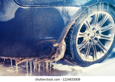 Close-up car wheel in icicles and freezing rain. Severe icing.