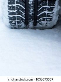 Closeup of car winter tires on the road covered with snow