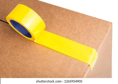 Closeup of cardboard box with yellow adhesive tape