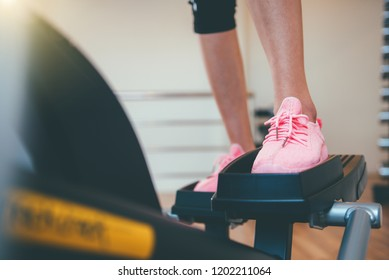 Closeup cardio workout Back view of attractive young people working out on an elliptical trainer in gym.
