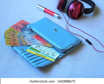 closeup cards (Australian driver licence, medicare, coffee cards) and some money in blue wallet