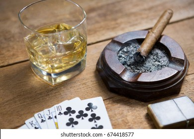 Close-up of cards by whisky and cigar on wooden table