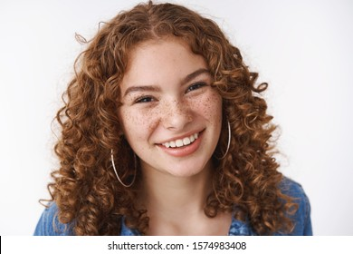 Close-up carefree smiling young female student curly-haired freckles acne prone skin smiling broadly friendly-looking camera hanging out friends playfully giggling, standing white background