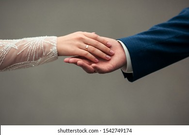 Close-up caressing hands of newlyweds. Gentle touch of hands of loving couple of newlyweds. Beautiful and romantic holding hands with woman`s hand on top of man`s hand with wedding rings on close up