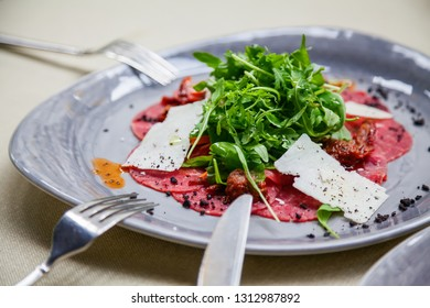close-up carpaccio meat with arugula and slices of parmesan cheese