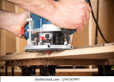 closeup of carpenter with hand wood router machine at work. closeup of routing a bevel into plank of pine woodworking construction tool concept furniture making diy background