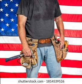 Closeup carpenter holding hammer and wearing worn out old, leather tool belt with hand tools in front of American flag, construction worker, patriotic, patriotism, usa, proud, trade union, craftsman