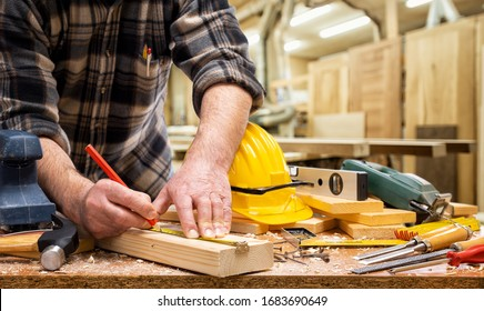 Close-up. Carpenter with pencil and the meter marks the measurement on a wooden board. Construction industry, carpentry workshop.