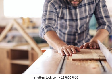 Closeup of a carpenter sawing a plank of wood with a table saw while working alone in his woodworking studio