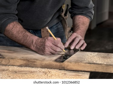 Closeup of carpenter, tool belt, and rough hands using pencil and old wooden handle square to mark line on a wood board to cut, during residential fixer upper home remodel construction