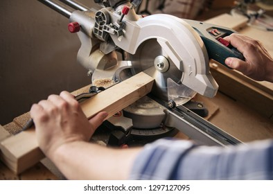 Closeup of a carpenter using a mitre saw to cut a piece of wood while working alone in his woodworking studio