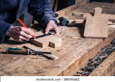 Close-up of a Carpenter Working on a Wooden Cutting Board with Pencil and Ruler in his Workshop; Selective Focus