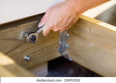 Closeup of carpenter's hand tightening bolt with wrench