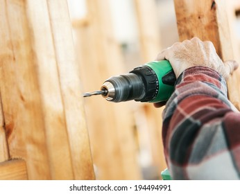 Closeup of a carpenter's hands using a drill on a construction site.  Focus on drill and hand.  Shallow depth of field.