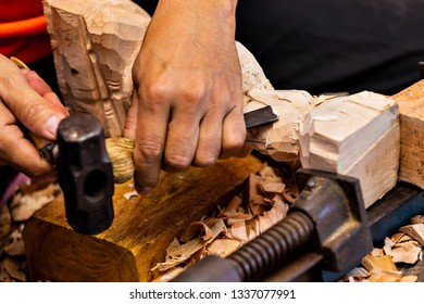 Closeup of a carpenter's hands working with a chisel and hammer on wooden buddha sculpture. Artisan woodcarver creates a lumber statuette.