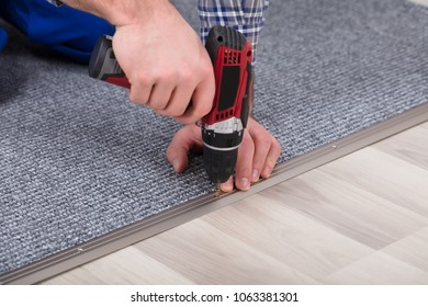 Close-up Of A Carpet Fitter's Hand Installing Grey Carpet With Wireless Screwdriver