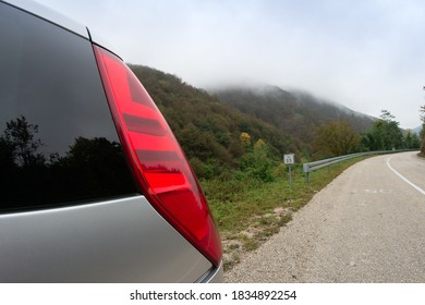 Close-up of a car's taillight on a mountain road. Car headlight with fog and mountains in the background. The concept of travel and wildlife exploration